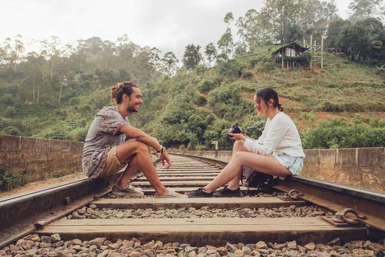 Friends sitting on railroad track by trees