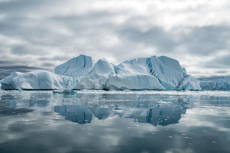 Icebergs Against Cloudy Sky