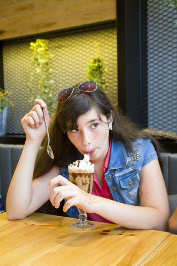 Young woman looking away while having dessert at cafe