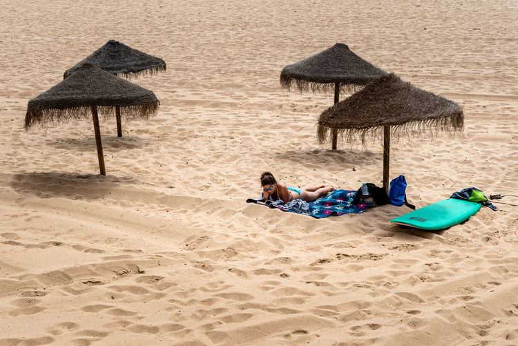 People relaxing on sand at beach
