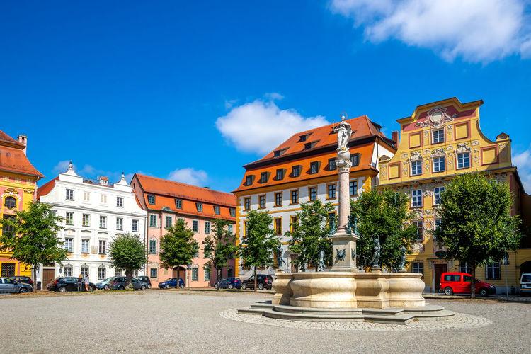Street by buildings against blue sky