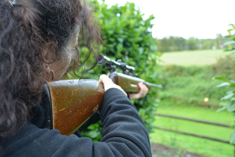 Cropped Image Of Woman Holding Rifle Aiming Against Trees At Park