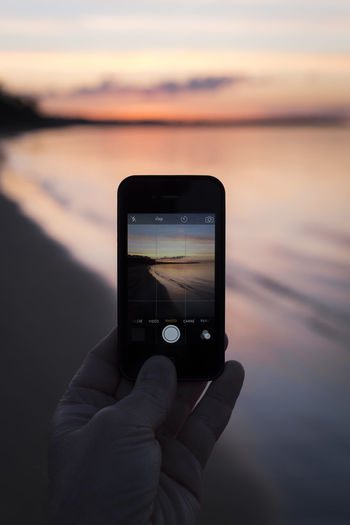 Close-up of hand holding smart phone at sunset