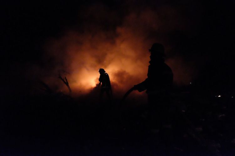 Silhouette Firefighters Against Sky At Night