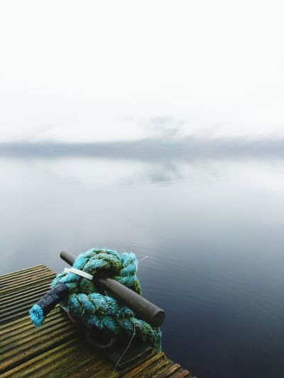 High angle view of rope tied on metal over lake against sky