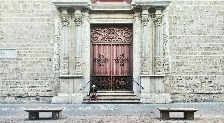 Man sitting at entrance of san martin de tours de fromista