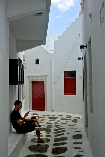 man sitting and watching the mobile in the street of Chora in Mykonos One Person Architecture Building Exterior Built Structure Building Real People Full Length Lifestyles Day Leisure Activity Nature Young Adult Outdoors Rear View Adult Entrance Door Casual Clothing Window Watching Mobile Greek Architecture Street View Mykonos,Greece Relaxing Moments Sitting Outside Sitting Alone Tourism Destination Red Doors