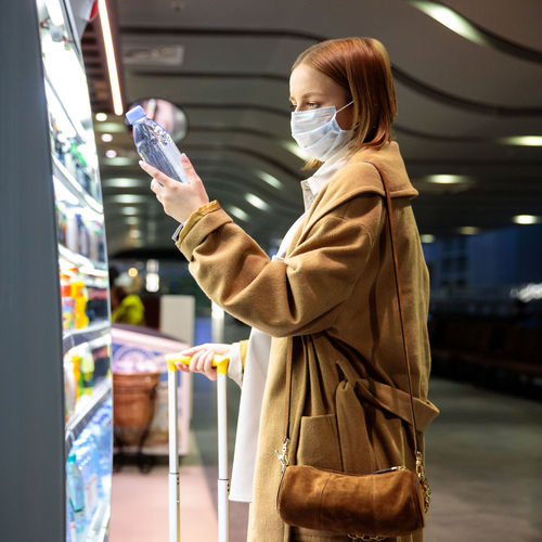 Side view of woman wearing mask buying water bottle at airport