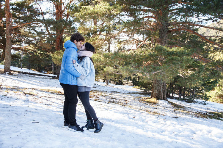 Full Length Side View Of Young Couple Falling In Love While Standing On Snow