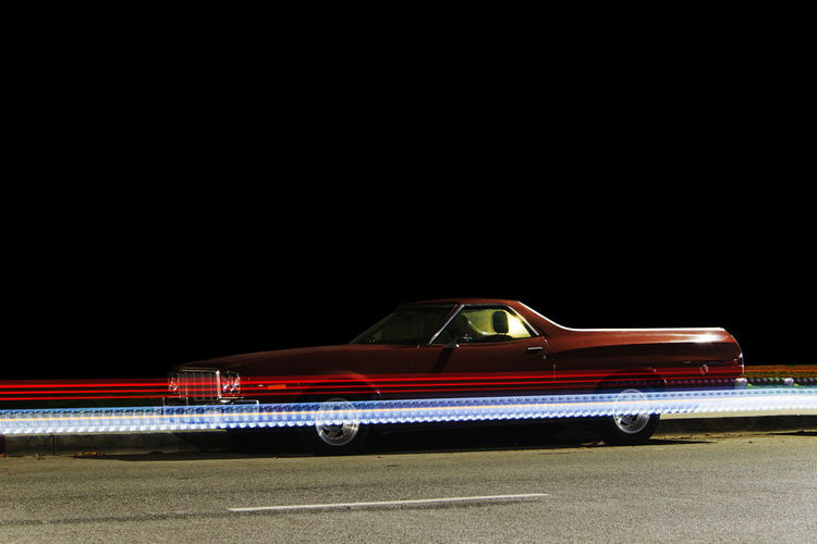 Side view of a vintage classic pick up truck car and light trails caused by traffic in Venice, California at night Car City Copy Space Illuminated Land Vehicle Mode Of Transportation Motion Motor Vehicle Night No People on the move Outdoors Red Road Street Tail Light Transportation