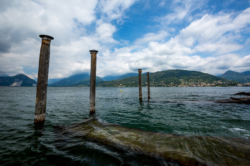 Wooden pillars and the shore of town Stresa on Italian Lago di Maggiore with the beautiful landscape of villas and parks on the lake on a background of green mountains as seen from Isola Bella. Naval Stresa Stresa Italy Architecture Beauty In Nature Built Structure Cloud - Sky Day Mountain Nature No People Non-urban Scene Outdoors Post Scenics - Nature Sea Sky Tranquil Scene Tranquility Water Waterfront Wood - Material Wooden Post