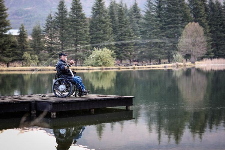 Full length of man sitting on wheelchair fishing at lake