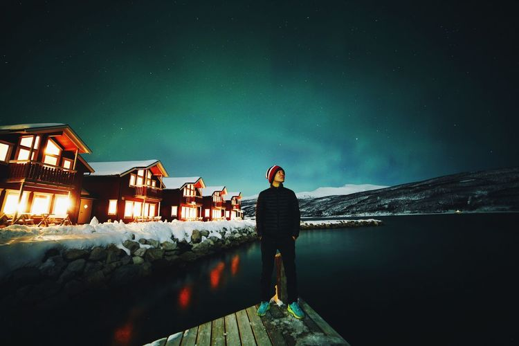 Rear view of woman standing on snow against sky at night