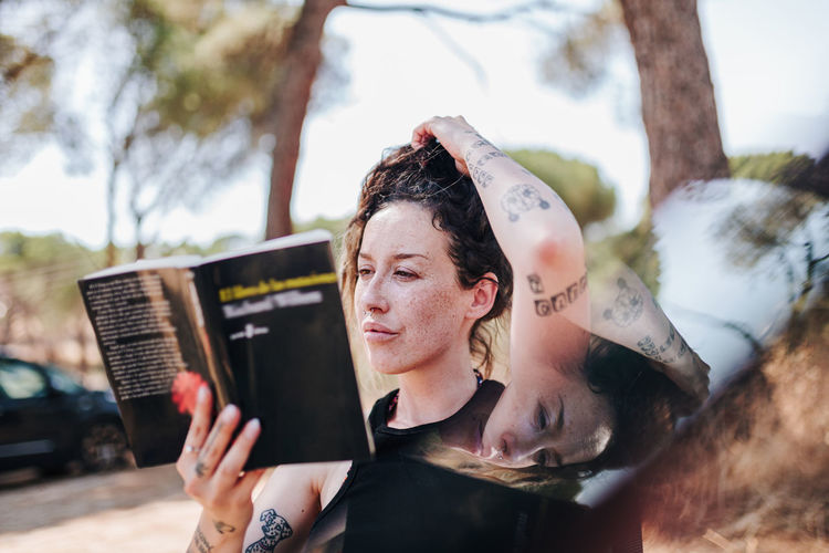 Woman reading book while sitting outdoors