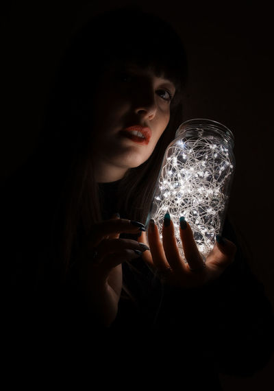 Portrait of young woman holding jar with illuminated string light against black background