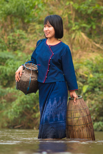 Woman with whicker baskets walking in river