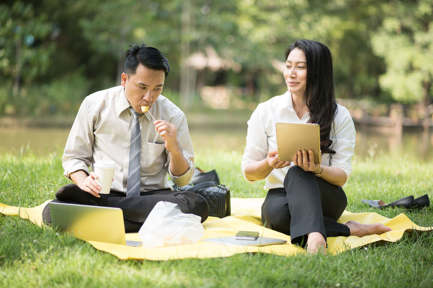 Business Business Person Businessman Businesswoman Communication Computer Corporate Business Day Digital Tablet Full Length Grass Holding Laptop Men Occupation Outdoors Real People Sitting Technology Togetherness Two People Using Laptop Wireless Technology Women Working