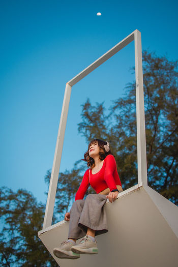 Low angle view of woman holding umbrella against blue sky