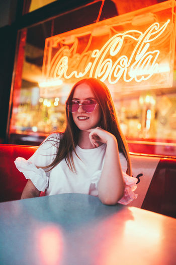Portrait of smiling woman sitting on table at restaurant