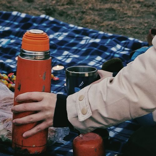 Cropped image of hand holding insulated drink container at picnic
