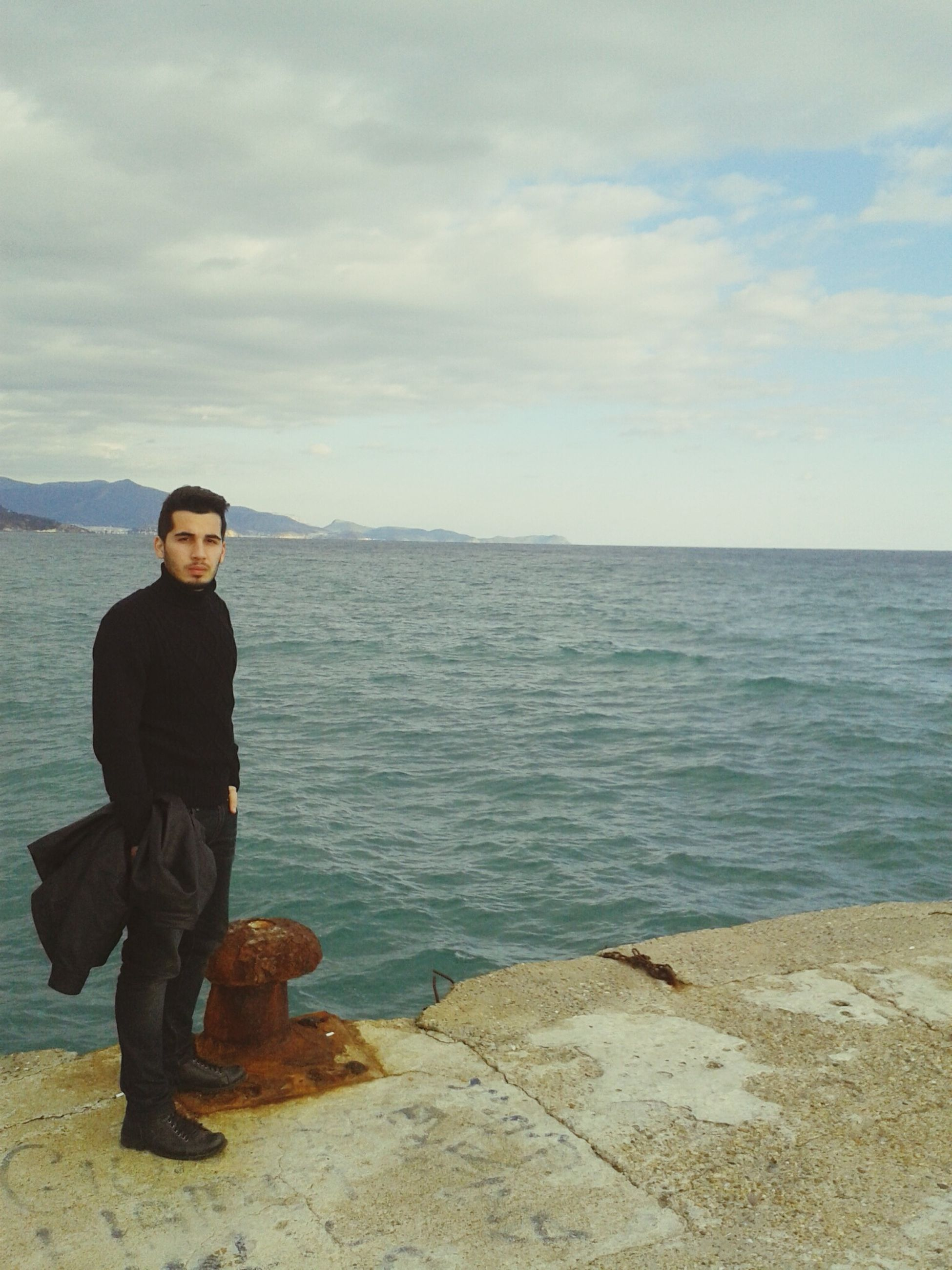 water, lifestyles, casual clothing, sea, leisure activity, standing, young adult, sky, person, full length, scenics, young men, beauty in nature, nature, tranquility, tranquil scene, cloud - sky