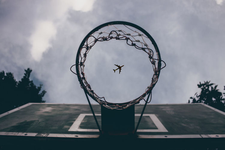 Directly below shot of airplane flying seen through basketball hoop against sky