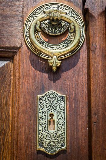 Close-up of door knocker on wooden wall of building