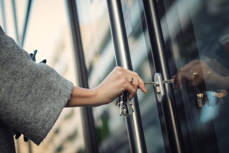 Cropped hand of woman opening door