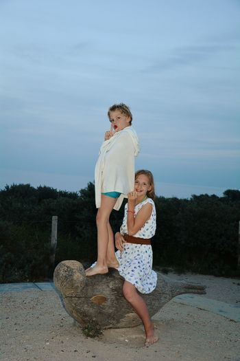 Portrait of happy siblings on wooden sculpture against sky at dusk