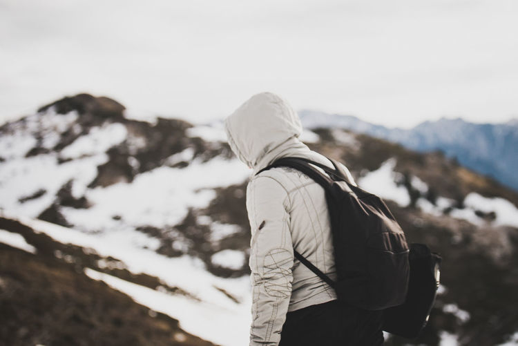 Side View Of Backpacker Wearing Hooded Jacket On Mountain