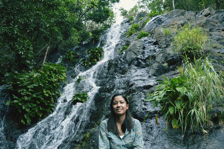 Portrait of smiling woman against waterfall in forest