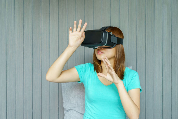 Woman wearing virtual reality simulator against wall