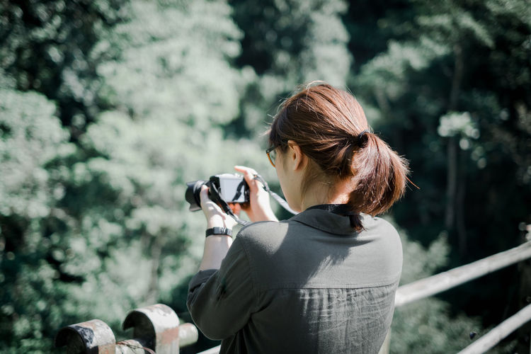 Woman photographing through camera while standing by railing on bridge