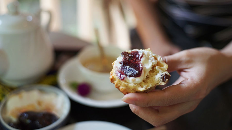 A woman holding a scone with jam on top Jam Bread Holding English British Bake Bakery Scones Scone Food And Drink Food Human Hand One Person Hand Holding Sweet Food Sweet Indulgence Close-up Healthy Eating Lifestyles Dessert Breakfast Finger Scone Jam Tea Cup Pot Woman