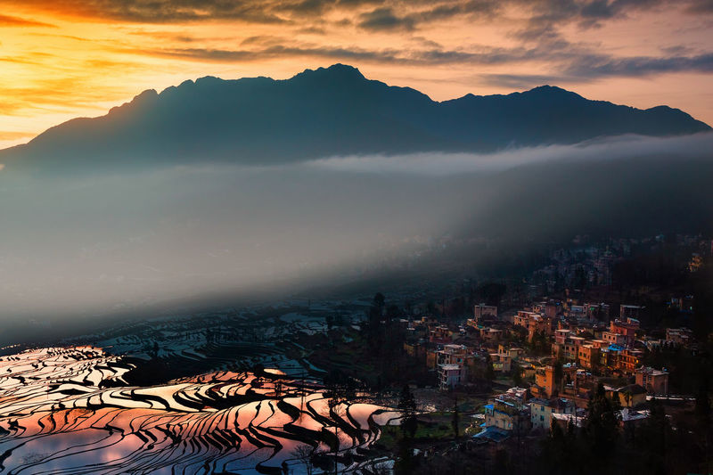 Beautiful morning sunrise with the mist shining on rice terrace in China. Agriculture Architecture Beauty In Nature Building Exterior Built Structure China City Cityscape Cloud - Sky Colorful Hazy  High Angle View Landscape Mist Mountain Mountain Range Nature No People Outdoors Rice Terraces Scenics Sky Sunrise, Sunset Valley Shades Of Winter