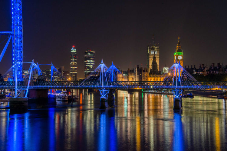 Illuminated hungerford bridge and golden jubilee bridges and houses of parliament in city at night