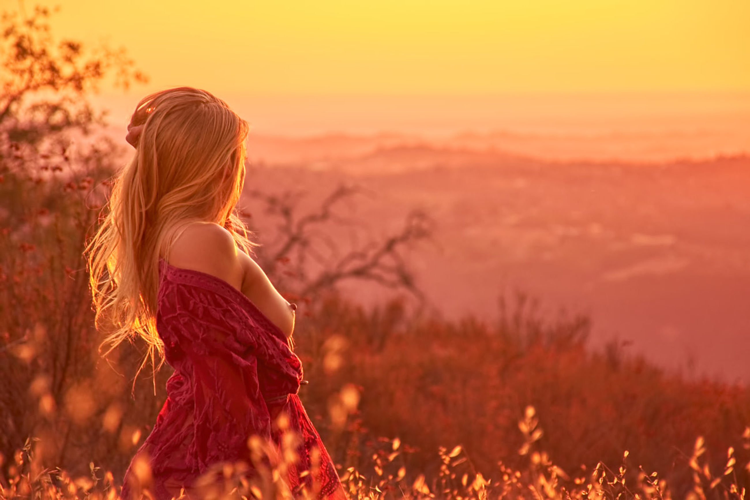 sunset, one person, real people, sky, leisure activity, lifestyles, orange color, land, women, beauty in nature, nature, hairstyle, three quarter length, hair, field, side view, long hair, adult, casual clothing, outdoors