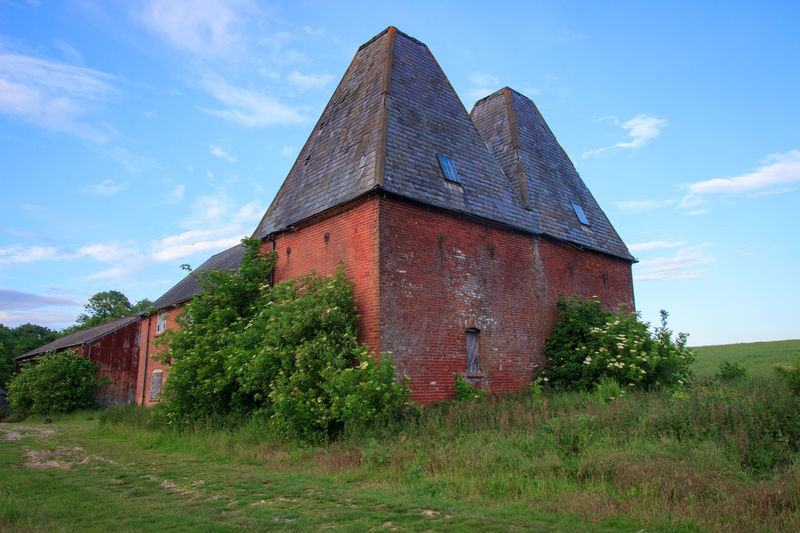 Oast House, Garden Of England, Kent, England. Architecture Sky Built Structure Nature No People Plant Hops Beer Brewing Iconic Buildings Vivid International Getty Images EyeEm Gallery Travel Destinations Tourism Sunrise Countryside Rural Scene History Grass Building Exterior Land Field Cloud - Sky Building Day Tree Landscape Old Abandoned Outdoors Growth Low Angle View