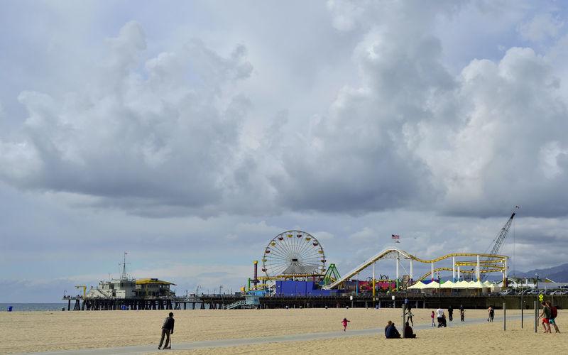 People Enjoying At Beach By Santa Monica Pier Against Sky