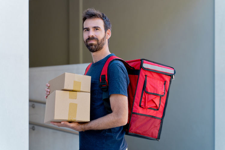 Portrait of man holding camera in box