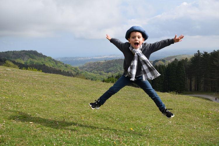 Full Length Portrait Of Boy Jumping Over Grassy Field Against Sky