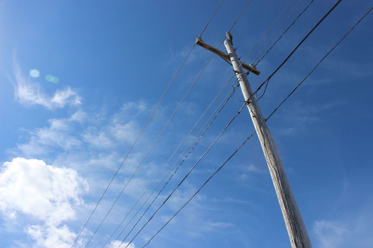 Low Angle View Of Electricity Pole Against Cloudy Sky