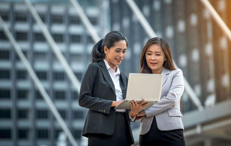 Business women working together. Business Business Person Businessman Businesswoman City Communication Cooperation Corporate Business Digital Tablet Downtown District Focus On Foreground Outdoors Partnership - Teamwork Professional Occupation Smiling Success Suit Teamwork Technology Togetherness Two People Well-dressed White Collar Worker Women Working