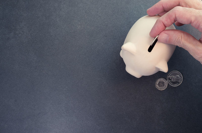 Close-up of hand putting coins in piggy bank over white background