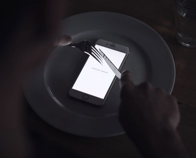 Cropped Image Of Man Holding Fork And Knife Over Smart Phone At Table