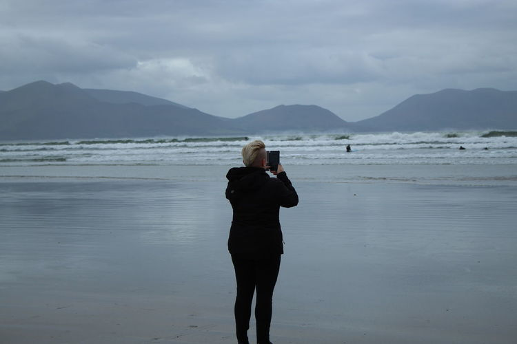 Rear view of woman photographing sea while standing at beach against sky