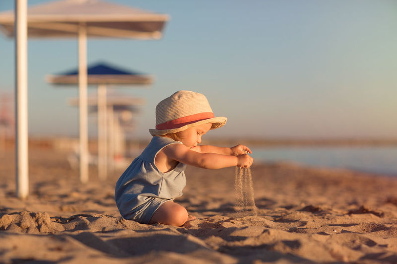 Boy wearing hat on sand at beach against sky