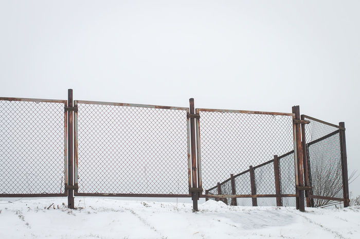Private property boarded by a metalic mesh fence constructed from sections. Captured in winter with white snow, overcast sky. Blank space.EyeEmNewHere Street Photography Mesh Fence Border Construction Camp Property Estate Winter Snow Blank Empty Area Land Europe Geometry Streight slope Minimalist Architecture The Graphic City