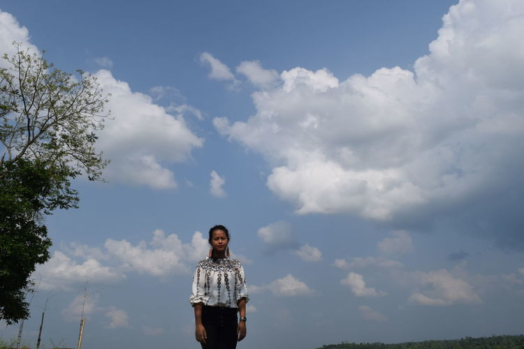 Portrait Of Young Woman Standing Against Cloudy Sky
