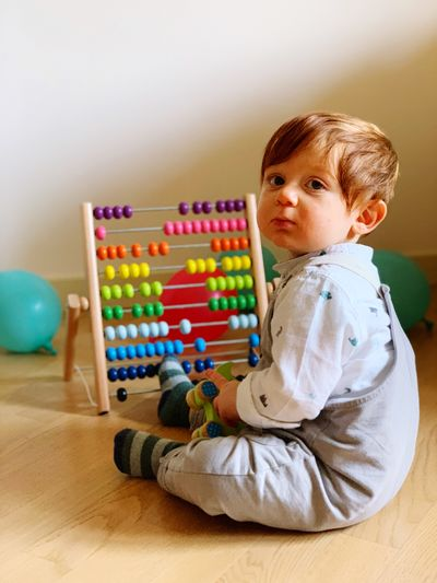 Cute boy playing with abacus at home